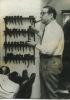 Simenon, chez lui, devant sa collection de pipes. SIMENON (Georges)